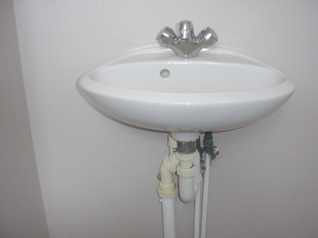 A wall hung basin located in a downstairs toilet of a house in East Kilbride that is about to be removed by A A MacMillan Plumbers