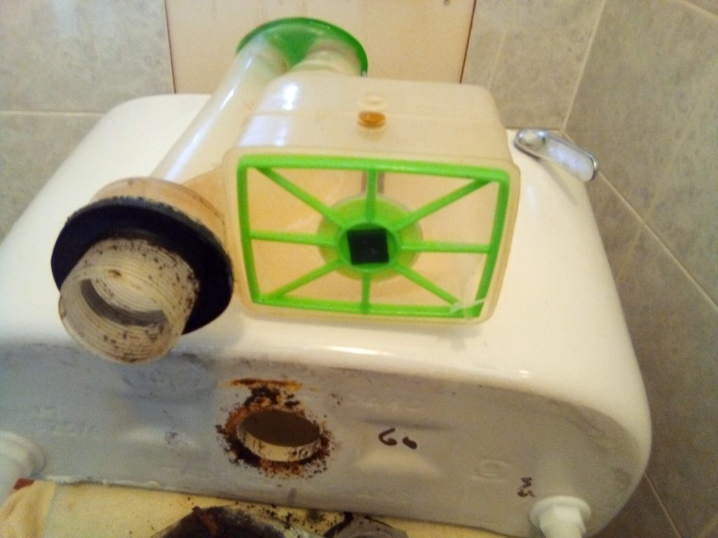 Close up view of a faulty toilet cistern syphon lying on top of a white ceramic Ideal Standard cistern. This flushing unit is being repaired by A A MacMillan Plumbers of East Kilbride