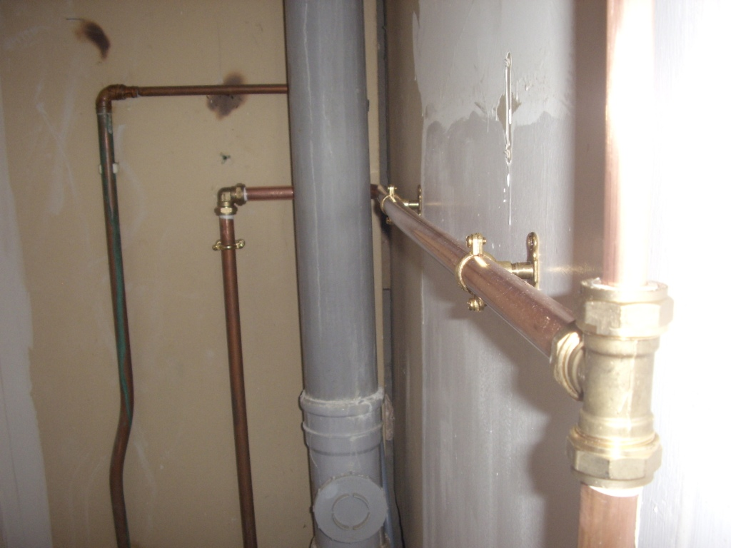 Copper pipework around a soil waste pipe inside a cupboard at a property in East Kilbride. Work carried out by A A MacMillan Plumbers