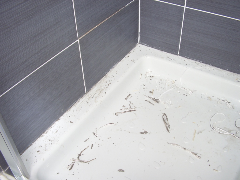 Old silicone sealant scraped off and removed from between the shower tray and tiling at a property in East Kilbride that A A MacMillan Plumbers were working in