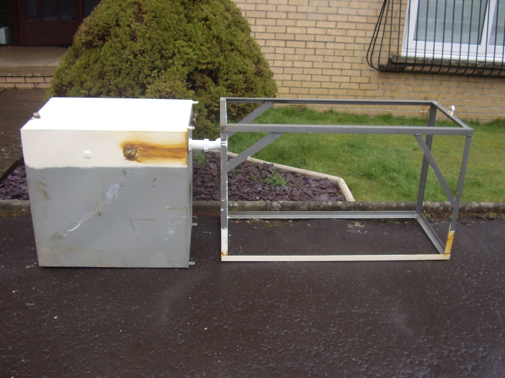 Rusted through water storage tank and stand lying on the pavement outside some flats in Brancumhall, East Kilbride. A A MacMillan Plumbers