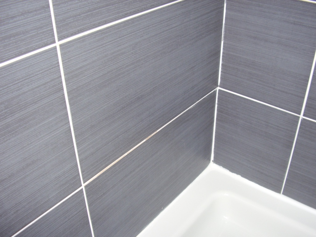Shower cabinet with a defective silicone seal between the tray and tiles. Areas of the grouting are also cracked and passing water in a property in East Kilbride