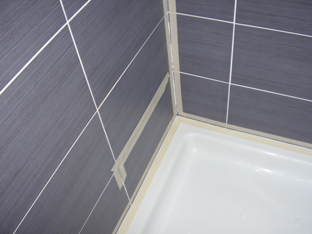 The shower tray and tiles have been thoroughly cleaned and have had masking tape applied to them ready for the application of the new silicone sealant by A A MacMillan Plumbers of East Kilbride