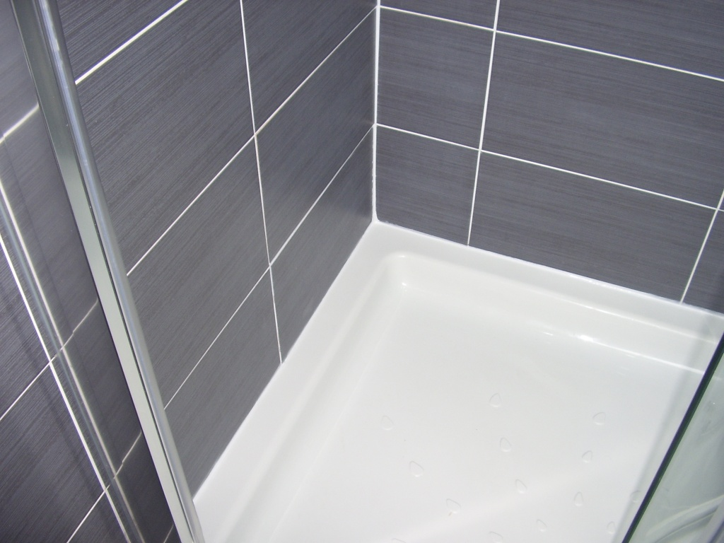 The shower tray has had a fresh bead of silicone sealant applied around it by A A MacMillan Plumbers of East KIlbride