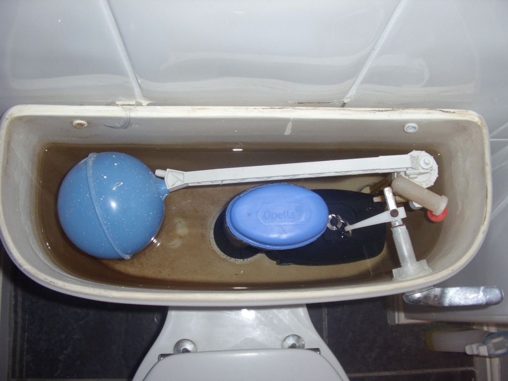 White ceramic Ideal Standard toilet cistern with the lid off, showing noisy float valve that is about to be replaced by A A MacMillan the plumber in a property in East Kilbride